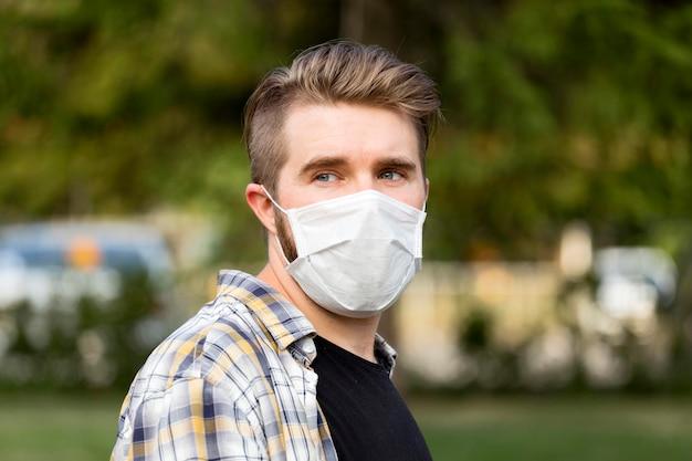 Portrait de jeune homme portant un masque facial