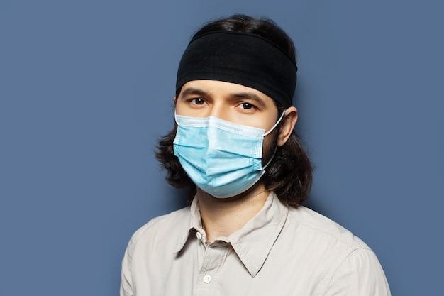 Portrait d'un jeune homme portant un masque médical sur le visage contre les virus sur fond de couleur bleue. vue rapprochée de la photo de studio.