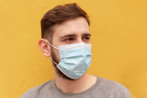 Portrait de jeune homme portant un masque médical