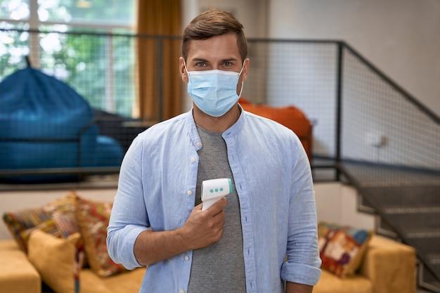 Portrait de jeune homme portant un masque de protection médical debout dans le bureau tenant l'infrarouge
