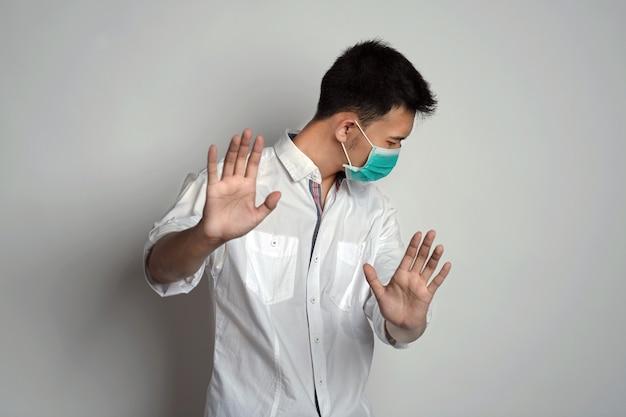 Portrait d'un jeune homme portant un masque de santé debout avec le visage tourné vers la gauche et montrant un refus