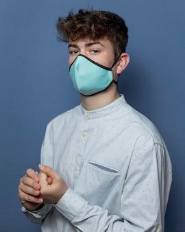 Portrait jeune homme portant un masque