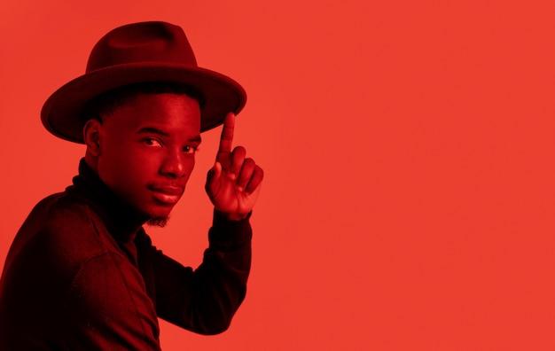 Portrait jeune homme posant avec chapeau