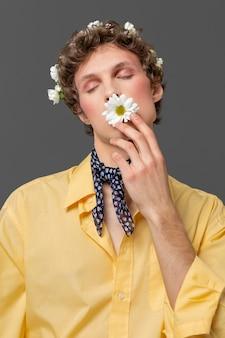 Portrait jeune homme posant avec une couronne florale