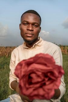 Portrait jeune homme posant avec fleur