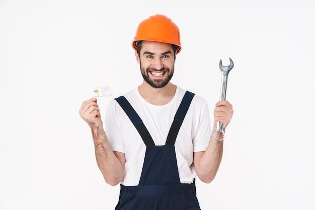 Portrait d'un jeune homme positif en casque isolé sur un mur blanc tenant une carte de crédit et une clé.