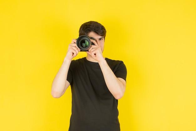 Portrait d'un jeune homme prenant des photos avec appareil photo contre jaune.