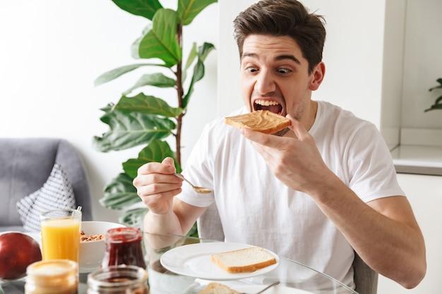 Portrait d'un jeune homme prenant son petit déjeuner