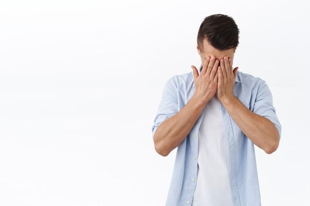 Portrait d'un jeune homme de race blanche déprimé et fatigué, se tenir la main sur le visage et soupirer, ressentir du regret ou du chagrin, se tenir debout en détresse, ressentir une dépression nerveuse, un épuisement professionnel, un mur blanc