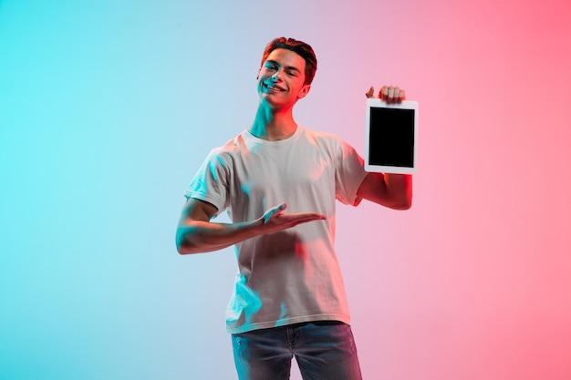 Portrait de jeune homme de race blanche sur fond de studio bleu-rose dégradé à la lumière du néon