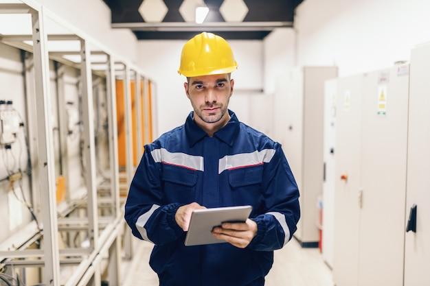 Portrait de jeune homme de race blanche habillé en vêtements de travail à l'aide de tablette en se tenant debout dans une usine de chauffage.