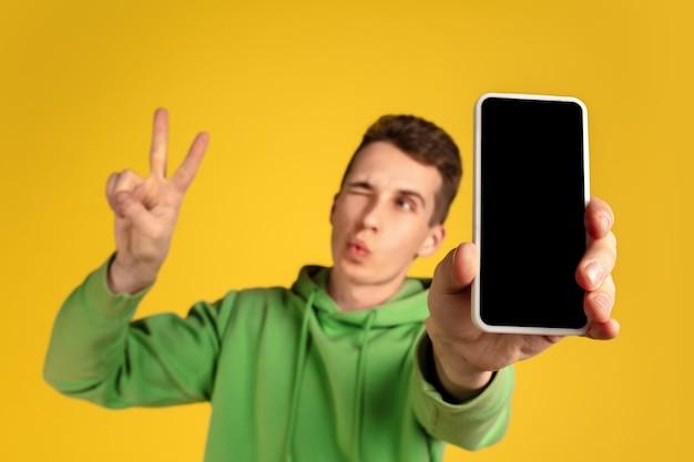 Portrait de jeune homme de race blanche isolé sur fond de studio jaune