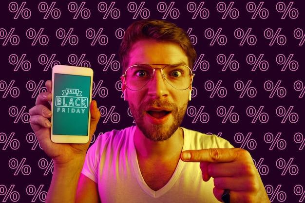Portrait de jeune homme de race blanche montrant l'écran du téléphone mobile sur fond violet avec des pourcentages. concept de vente, vendredi noir, cyber lundi, finance, entreprise. boutiques en ligne et facture de paiements.