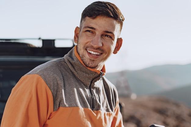 Portrait d'un jeune homme de race blanche en randonnée dans les montagnes se bouchent