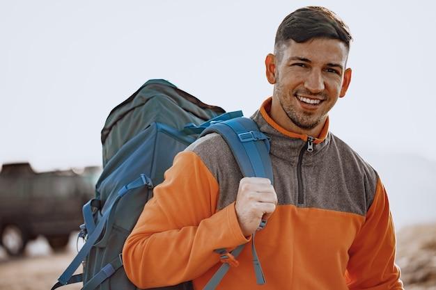 Portrait d'un jeune homme de race blanche en randonnée dans les montagnes