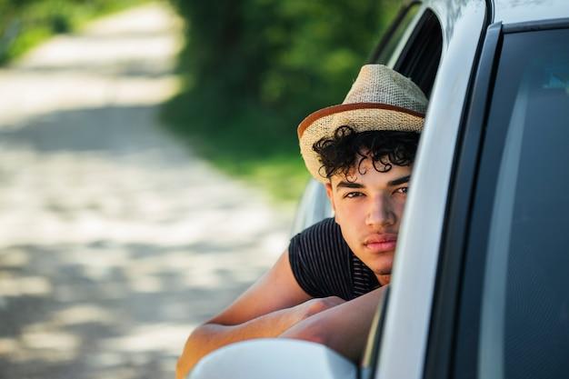 Portrait de jeune homme à la recherche de la fenêtre de la voiture