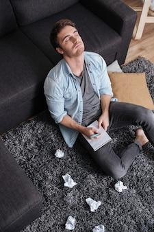 Portrait d'un jeune homme réfléchi assis sur un tapis avec les yeux fermés et tenant le bloc-notes