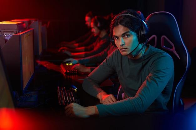 Portrait de jeune homme regardant la caméra alors qu'il était assis sur une chaise en face de l'ordinateur et jouer au jeu