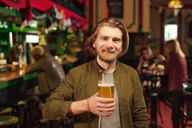 Portrait de jeune homme regardant la caméra et buvant de la bière au bar