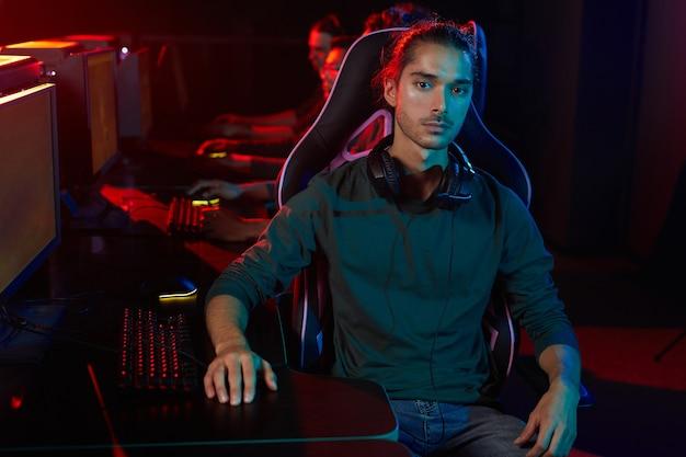 Portrait de jeune homme regardant la caméra pendant son jeu en club informatique