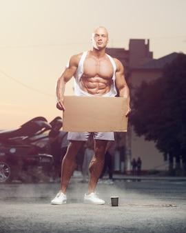 Portrait de jeune homme de remise en forme avec carton à la rue. panneau de signalisation dans la salle de sport. concept de musculation