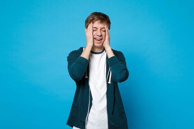 Portrait de jeune homme riant dans des vêtements décontractés en gardant les yeux fermés, mettant les mains sur le visage isolé sur le mur bleu.