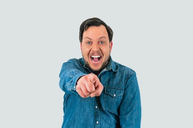 Portrait de jeune homme riant et pointant du doigt la caméra se moquant. chemise en jean et fond blanc isolé.