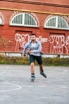 Portrait d'un jeune homme rollers dans le skate park