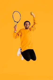 Portrait jeune homme sautant avec raquette de tennis