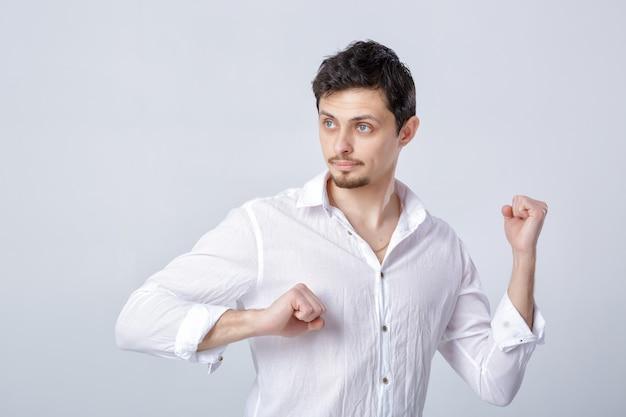 Portrait de jeune homme séduisant aux cheveux noirs dans une chemise blanche prête à se battre sur fond gris.