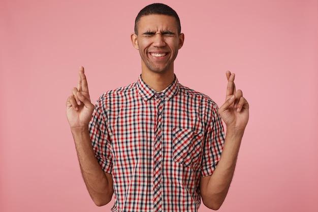 Portrait de jeune homme séduisant à la peau sombre en chemise à carreaux, avec les doigts croisés et les yeux fermés, espère la chance et les sourires, se dresse sur fond rose.