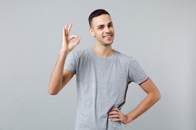 Portrait d'un jeune homme séduisant en vêtements décontractés, debout, montrant le geste ok