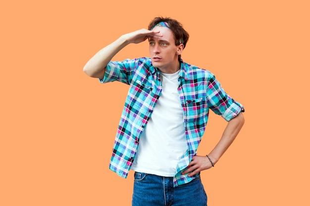 Portrait d'un jeune homme sérieux et attentif dans un bandeau de chemise à carreaux bleu décontracté, debout avec la main sur le front et regardant trop loin pour trouver quelque chose. tourné en studio intérieur, isolé sur fond orange.