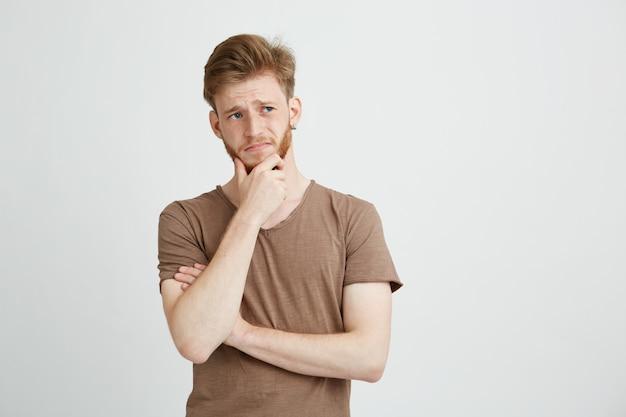 Portrait d'un jeune homme sérieux pensant à la recherche de côté.