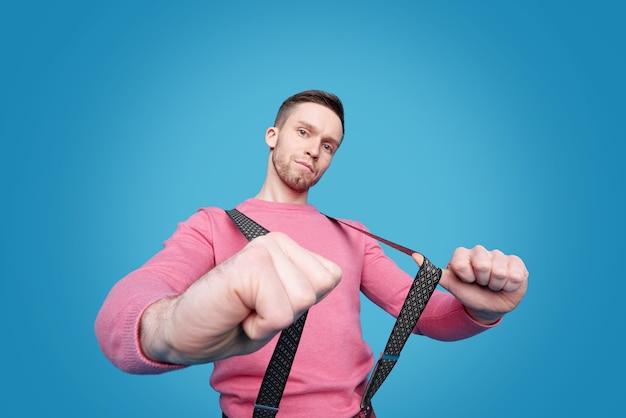 Portrait de jeune homme sérieux en pull rose tirant des bretelles de pantalon