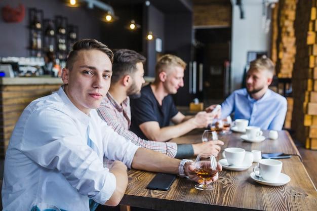 Portrait de jeune homme avec ses amis tenant un verre de boisson