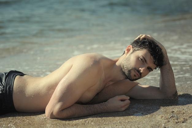 Portrait de jeune homme sexy portant dans l'eau de mer, topless, corps humide