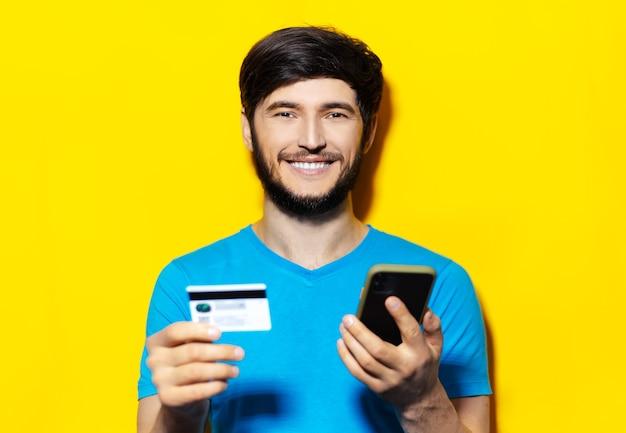 Portrait de jeune homme souriant en chemise bleue à l'aide de smartphone et carte de crédit