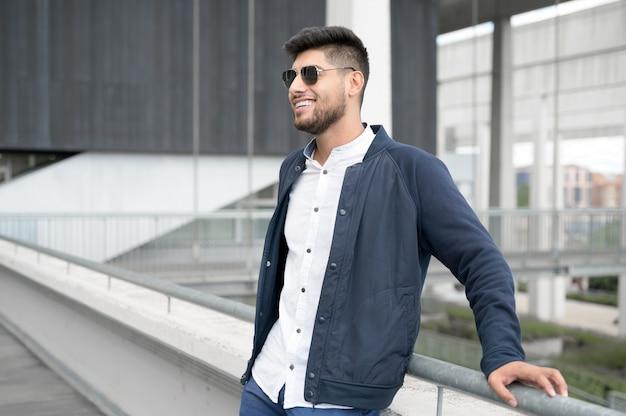 Portrait d'un jeune homme souriant et confiant, debout à côté d'un bâtiment moderne, regardant au loin