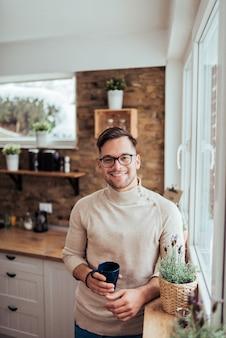 Portrait d'un jeune homme souriant dans des vêtements décontractés beiges, debout près de la fenêtre, tenant une chope et regardant la caméra dans la cuisine rustique moderne.