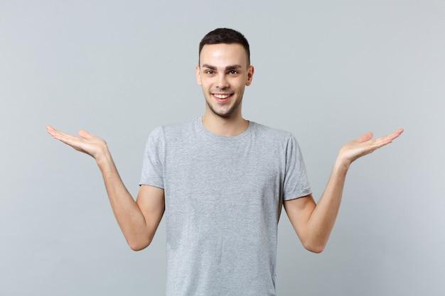 Portrait de jeune homme souriant dans des vêtements décontractés, écartant les mains pointant de côté