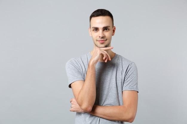 Portrait de jeune homme souriant dans des vêtements décontractés mis la main sur le menton