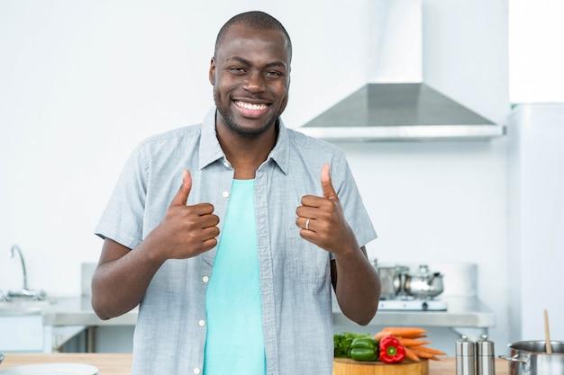 Portrait de jeune homme souriant, gesticulant pouce en l'air dans la cuisine à la maison