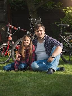 Portrait d'un jeune homme souriant et d'une jolie fille se reposant sur l'herbe au parc après avoir fait du vélo