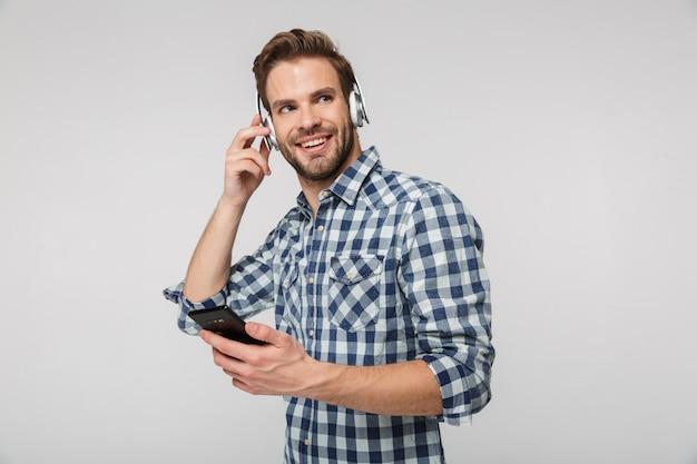 Portrait de jeune homme souriant portant des écouteurs utilisant un téléphone portable isolé sur un mur blanc