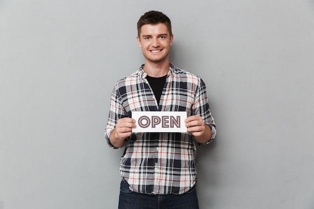 Portrait d'un jeune homme souriant avec signe ouvert