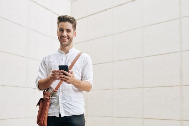 Portrait d'un jeune homme souriant avec un smartphone à l'aide d'une application mobile