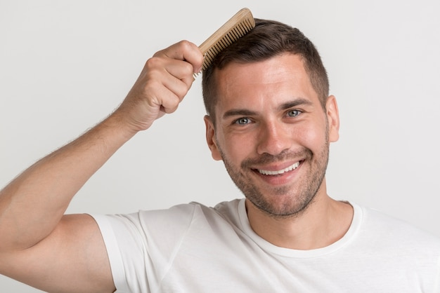 Portrait de jeune homme souriant en t-shirt blanc peigne ses cheveux