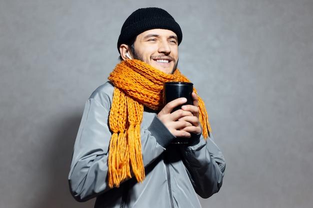 Portrait de jeune homme souriant avec tasse de café thermo dans les mains, avec des écouteurs sans fil