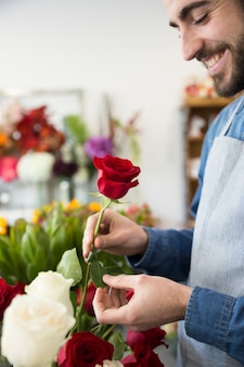Portrait d'un jeune homme souriant tenant une rose rouge à la main